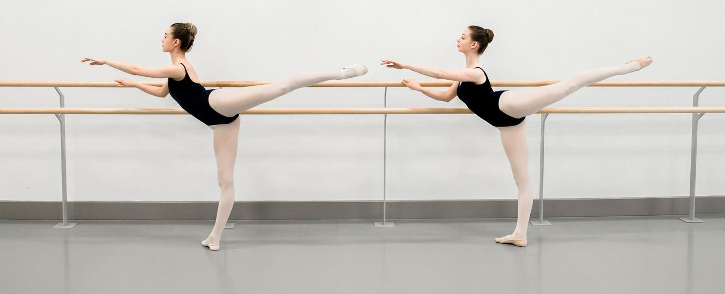 Two dancers posing at a barre