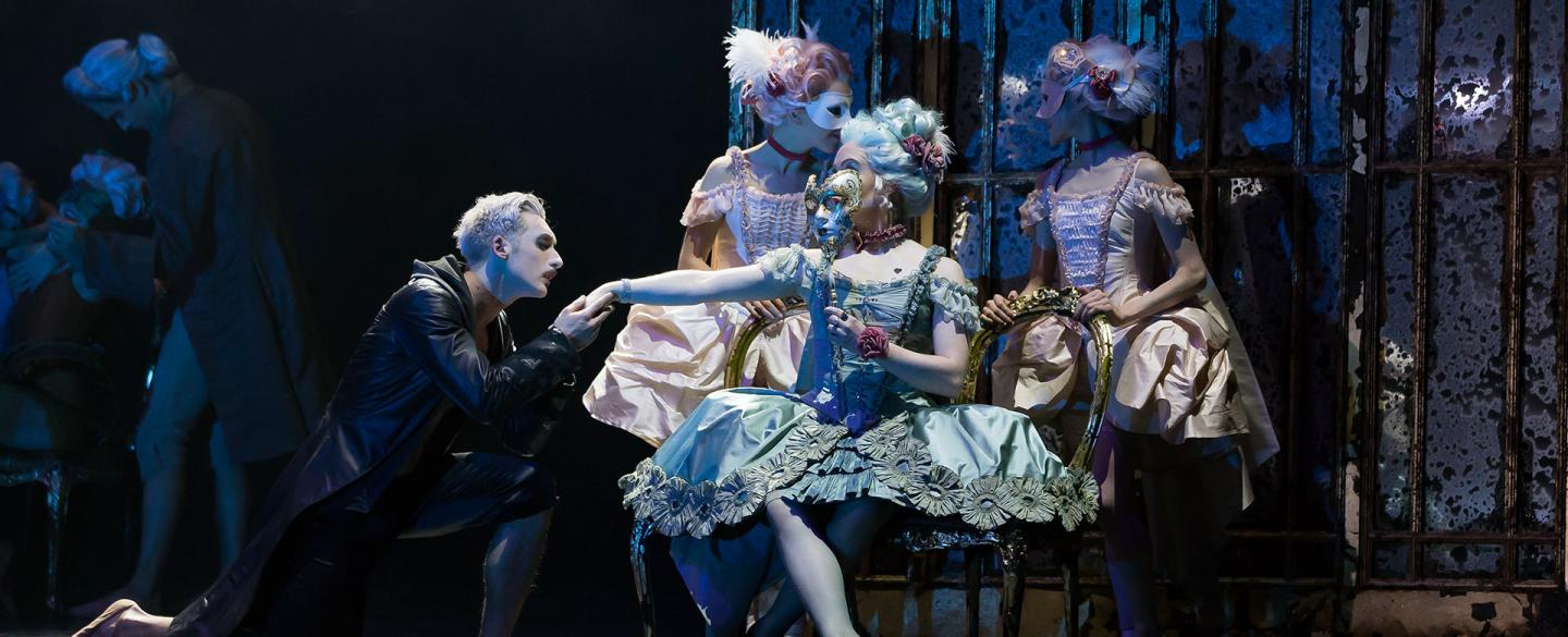 Casanova goes down on one knee as his kisses the back of masked Madame de Pompadour's hand