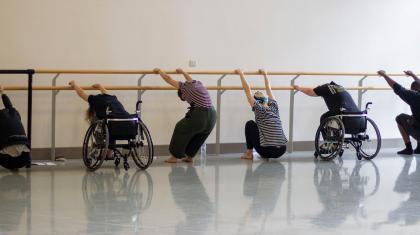 Two people in wheelchairs and three people standing, all stretching against a ballet barre