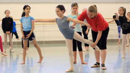teacher coaching child on dance position