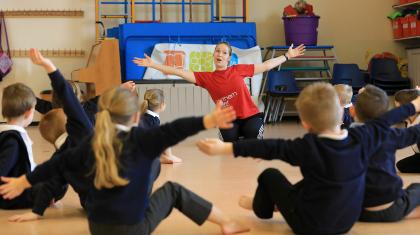 school children sat on floor with arms stretched out as teacher demonstrates in front of them
