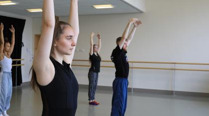 Students in a dance studio, stood still with arms raised above their heads