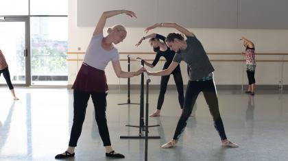 Dancers stretching at the barre in the Academy's adult class. Photo Kathie Tiffany.