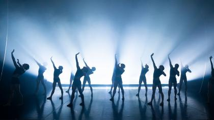 Northern Ballet dancers perform in unison through a flood of light. Photo Emma Kauldhar.