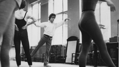 Laverne Meyer demonstrates a dance move to a full rehearsal room