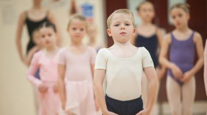 A boy stood with arms held in ballet position