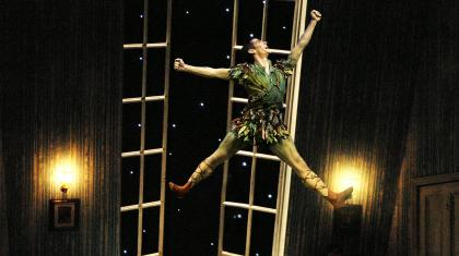 Ashley Dixon as Peter Pan leaps high in the Darling children's bedroom