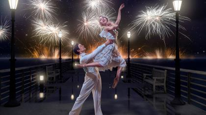 Male dancer holds female dancer aloft on a pier with fireworks in the sky