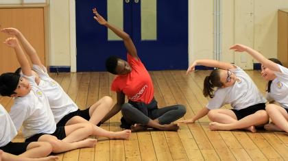 A group of students with a Northern Ballet Dance Education Officer. They are sat on the floor of their school hall, reaching one arm over their heads and across to the opposite side.